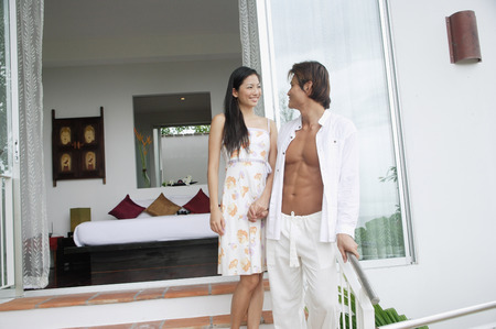 fully unbuttoned: Couple standing on steps outside of bedroom, holding hands