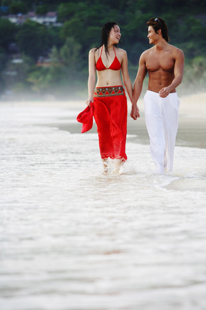 ankle deep in water: Couple walking, holding hands, along beach LANG_EVOIMAGES