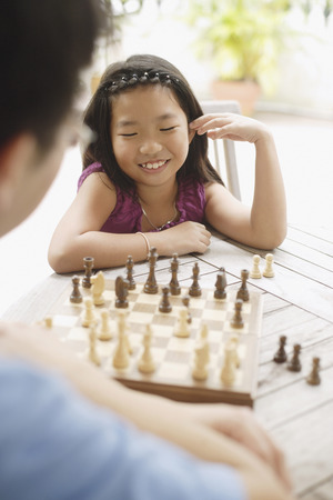 Father and daughter playing a game of chess