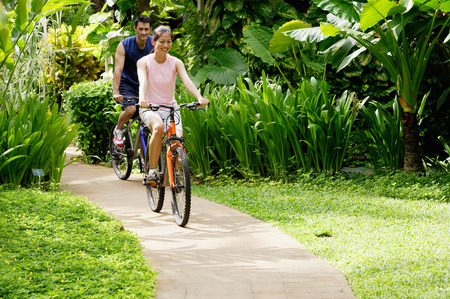 Young couple cycling through a park, smiling