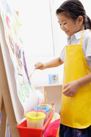 easel: Young girl in yellow apron,  painting on easel