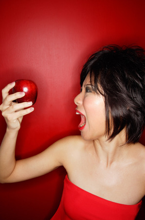 red tube: Woman in red tube tope holding red apple, mouth open LANG_EVOIMAGES