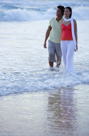 ankle deep in water: Couple walking on beach, ankle deep in water