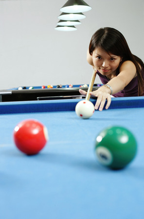 Woman holding pool cue, aiming at ball Stock Photo
