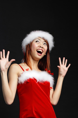Woman wearing Santa hat and red dress, mouth open in surprise Stock Photo