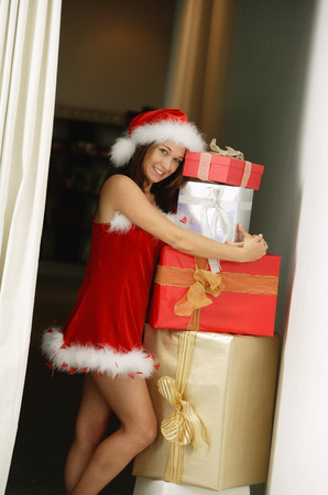 Woman in Santa hat and red dress embracing gift boxes
