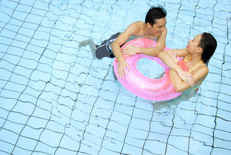 Couple in swimming pool leaning on inflatable ring Stock Photo