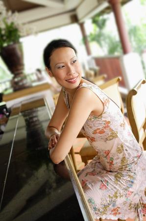 over the shoulder: Woman sitting at bar, leaning on counter, looking over shoulder LANG_EVOIMAGES