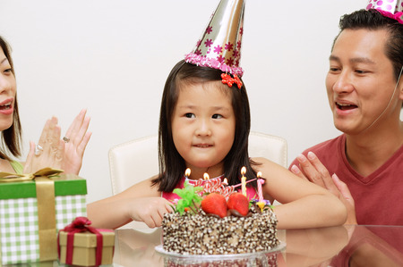 Girl with birthday cake, parents on either side clapping