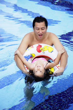 Father and daughter in swimming pool, daughter using inflatable ring Stock Photo