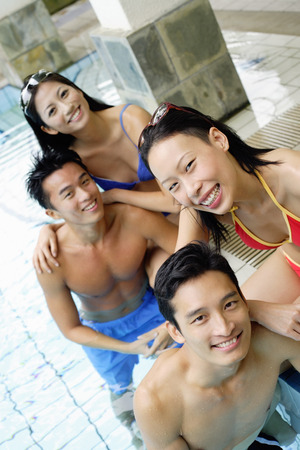 waist deep: Young adults in swimming pool, smiling at camera