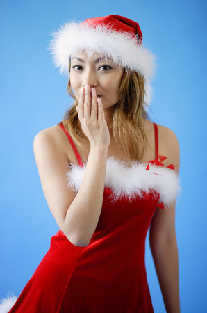 Woman wearing Santa hat and red dress, hand covering mouth