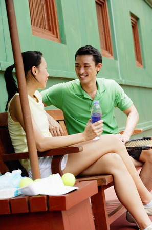 Couple sitting on bench on tennis court, smiling at each other, woman with legs crossed