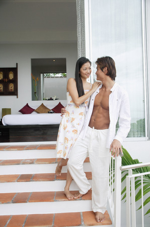 fully unbuttoned: Couple standing on steps outside of bedroom, looking at each other