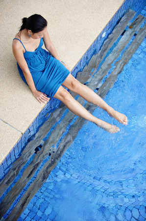 ankle deep in water: Young woman sitting by swimming pool, dipping feet in water
