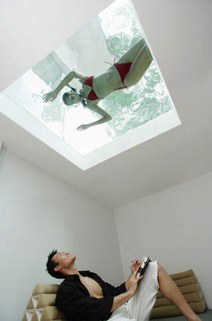 fully unbuttoned: Man looking at woman in swimming pool through the skylight