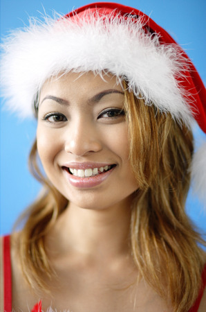 Woman wearing Santa hat, smiling at camera