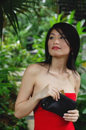 clutch bag: Woman in red dress, holding clutch bag, standing in garden LANG_EVOIMAGES