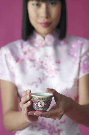 Woman holding Chinese tea cup towards camera Stock Photo