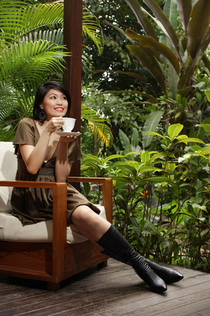 knee boots: Woman sitting on patio, having cup of tea