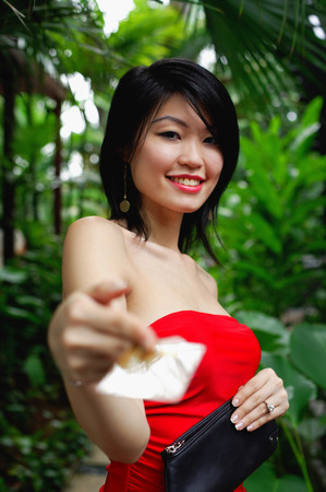 red tube: Woman in red tube top, holding credit card towards camera LANG_EVOIMAGES
