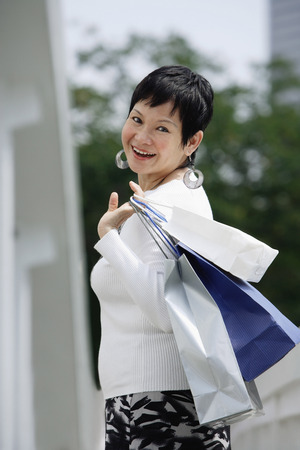 Mature woman carrying shopping bags, looking over shoulder LANG_EVOIMAGES