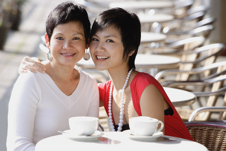 Mother and adult daughter in cafe, smiling at camera