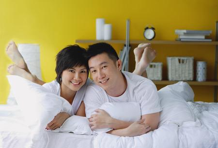 Couple lying on bed, portrait Banco de Imagens