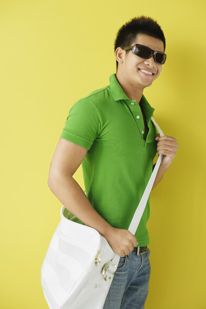 Man in green polo shirt, standing against yellow background, sunglasses on