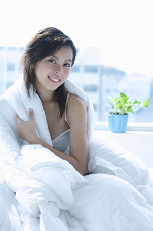 Young woman sitting on bed, wrapped in a blanket, smiling at camera