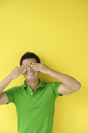 covering eyes: Man standing against yellow wall, covering eyes