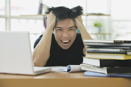 Young adult with laptop and books, hands in hair, grimacing