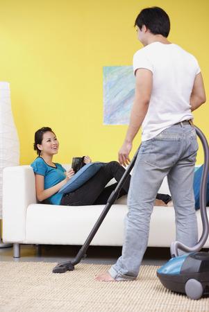 Man vacuuming, woman sitting on sofa with book, smiling at him