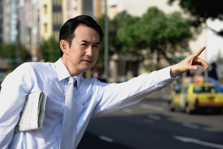 Businessman with newspaper under his arm, flagging a cab LANG_EVOIMAGES