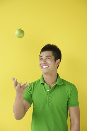 tossing: Man tossing green apple LANG_EVOIMAGES