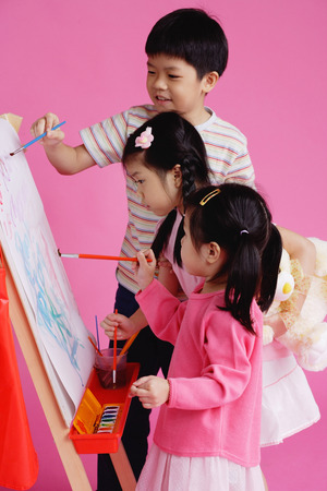three children: Three children painting on easel LANG_EVOIMAGES