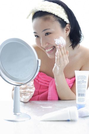 Young woman sitting at dressing table, putting lotion on face Stock Photo