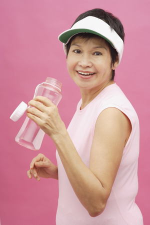 visor: Mature woman wearing sun visor and water bottle LANG_EVOIMAGES
