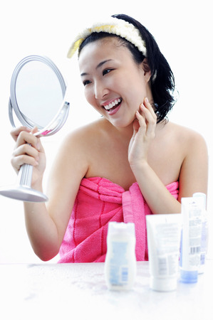 dressing table: Young woman sitting at dressing table, looking in mirror, hand on chin