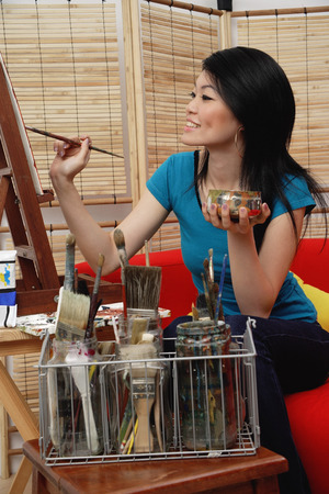 easel: Woman painting on easel LANG_EVOIMAGES
