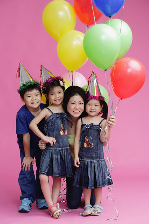 6 9 years: Mother and three children, posing with balloons LANG_EVOIMAGES