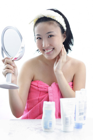 dressing table: Young woman sitting at dressing table, hand on chin, holding mirror
