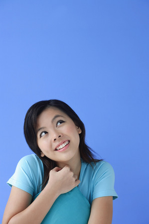 Young woman with pillow, against blue background