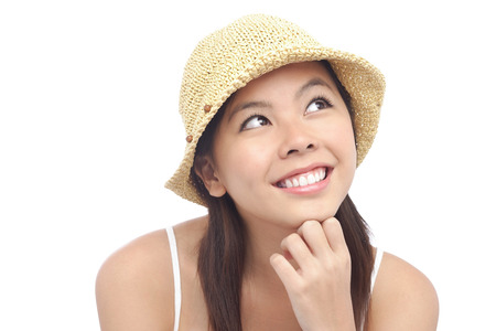 Young woman wearing hat, looking away, hand on chin LANG_EVOIMAGES