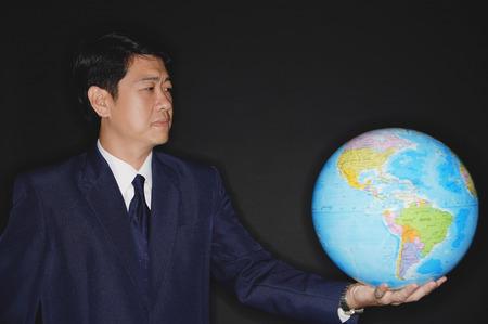world at your fingertips: Businessman holding globe