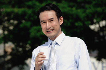 disposable cup: Businessman holding disposable cup, smiling at camera