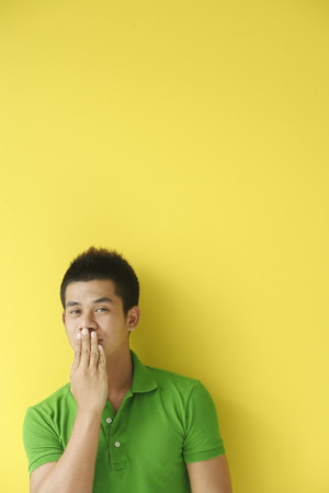 Man standing against yellow wall, covering mouth