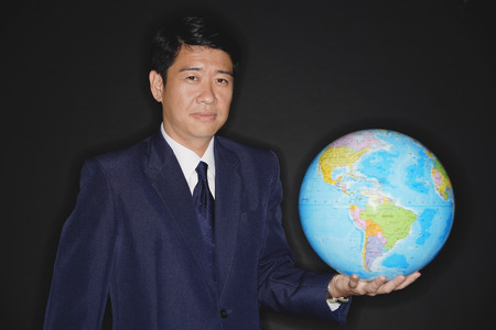 world at your fingertips: Businessman holding globe, looking at camera LANG_EVOIMAGES