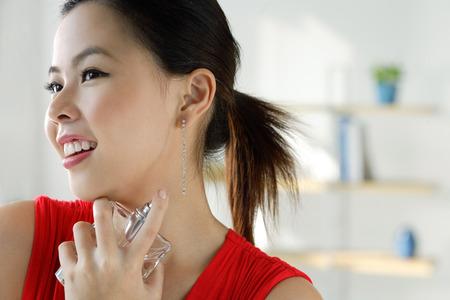 Young woman spraying perfume Banco de Imagens