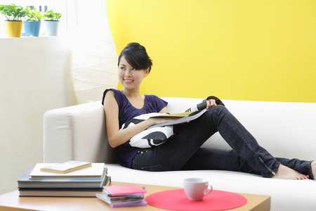 Woman sitting on sofa, looking away Stockfoto